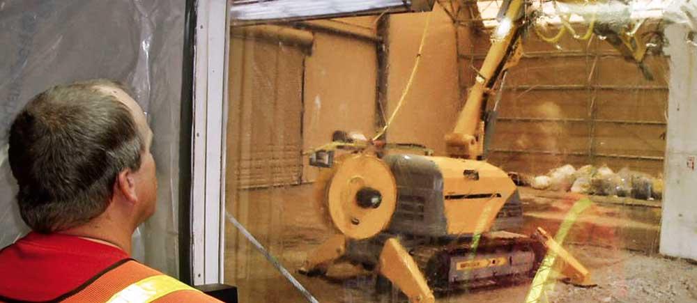Riving av ett radioaktivt rom bak akrylglass